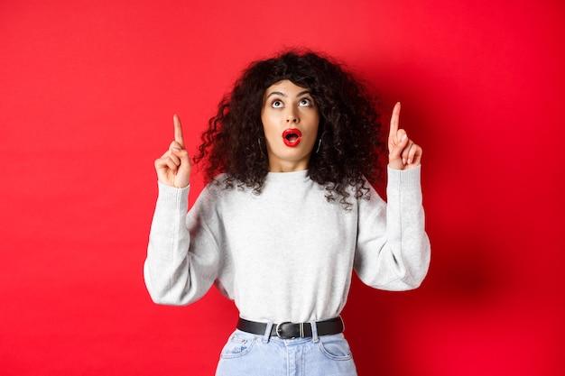 Впечатленная европейская женщина-модель в повседневной одежде, смотрит промо с отвисшей челюстью, смотрит и показывает пальцами вверх, показывает логотип, стоит на красном фоне