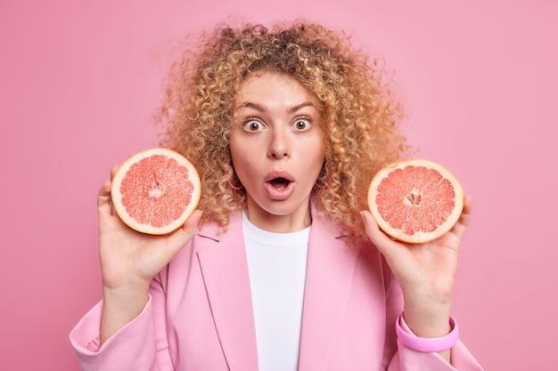 La donna europea impressionata tiene in mano due metà di pompelmo fresco sorpresa di scoprire sostanze utili che questo agrume contiene ha i capelli ricci isolati sul muro rosa. dieta