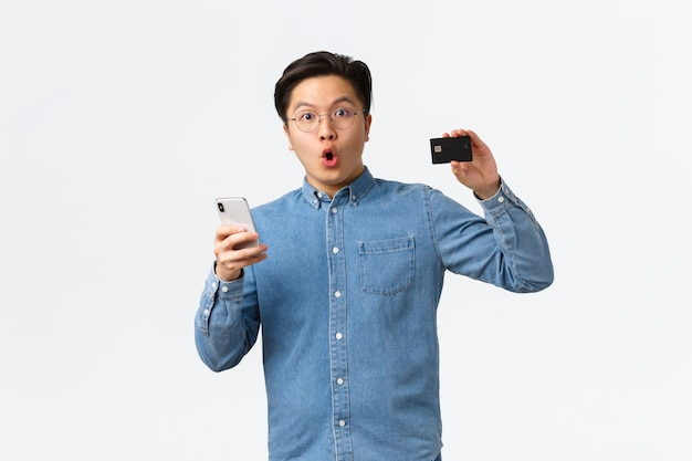Cliente di banca asiatica impressionato ed entusiasta, ragazzo con gli occhiali e abbigliamento casual che mostra la carta di credito mentre utilizza lo smartphone per aprire l'applicazione di e-banking, lo shopping in internet con l'app mobile.