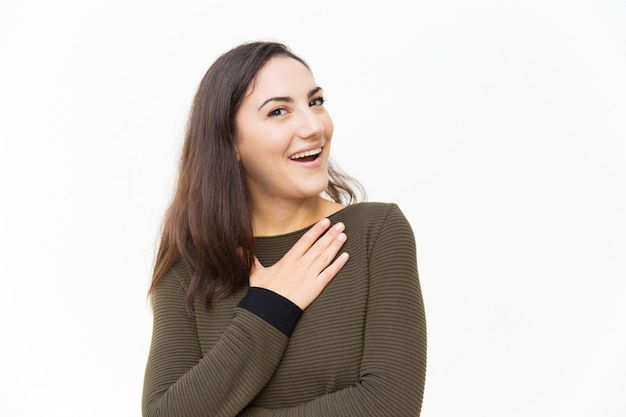 Impressed excited beautiful woman keeping hand on chest
