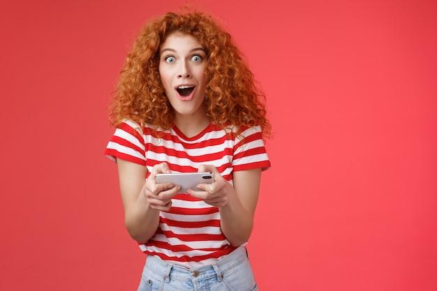 Впечатлила возбужденная симпатичная рыжая кудрявая женщина, держащая смартфон горизонтально с открытым ртом, очаровала ...