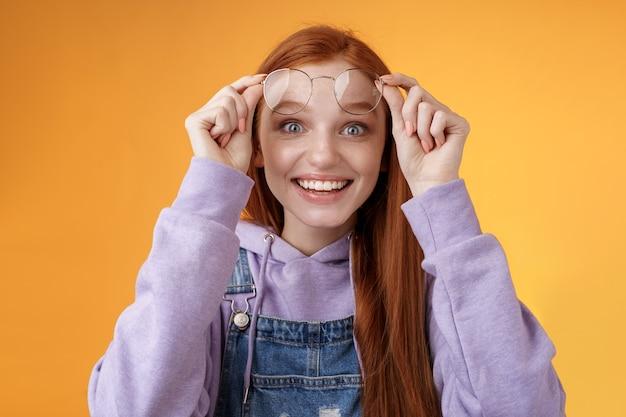感動した興奮した幸せな若い愚かな素敵な赤毛の女の子は、喜ばしい驚きを受け取りますメガネを外しますコピースペース