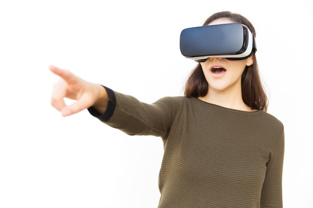 Impressed excited woman in vr headset pointing finger away