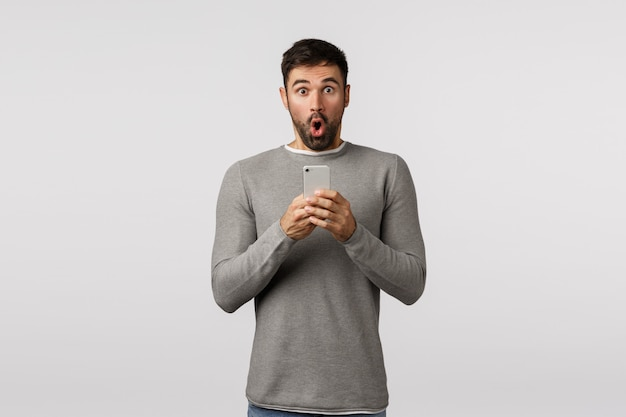 Impressed and fascinated excited, bearded caucasian man in grey sweater take out his phone to record amazing event, folding lips gasping, say wow omg, hold smartphone, photographing awesome thing