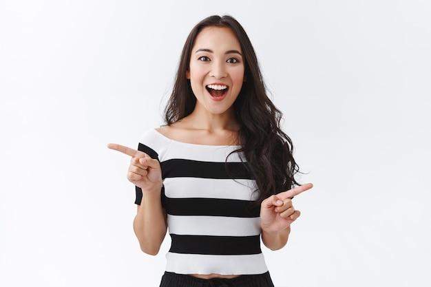 横向きの縞模様のtシャツを着た、感動した、魅了された見栄えの良い東アジアの女の子、左右の広告を表示し、面白がって驚いて笑って、カメラを楽しませて、白い背景を見てください