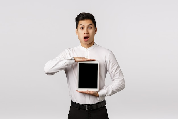 Impressed, fascinated handsome asian guy in formal outfit introduce amazing new application, showing shopping site or link on gadget screen, holding digital tablet, say wow excited