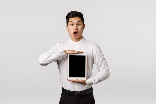 Впечатленный, очарованный красивый азиатский парень в официальном наряде представляет удивительное новое приложение, показывающее сайт покупок или ссылку на экране гаджета, с цифровым планшетом и, скажем, в восторге
