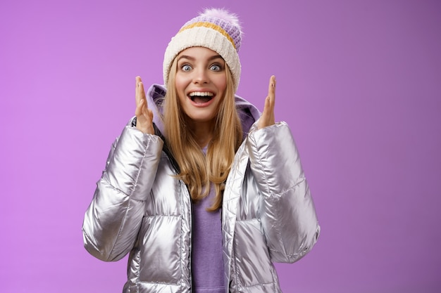 Impressed fascinated speechless attractive blond girl explaining awesome situation shaking hands excited smiling gasping happily widen eyes surprised, standing purple background amused.