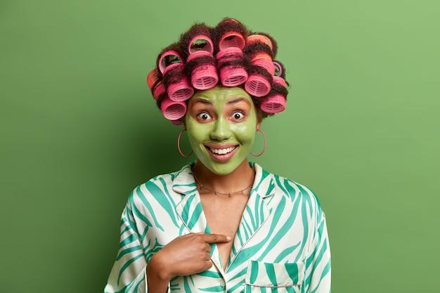 La donna colpita indica se stessa, essere scelta felice non può credere nel proprio successo sembra allegra, indossa una maschera di bellezza applicata sul viso per i bigodini della pelle impeccabili. donne, acconciatura, spa