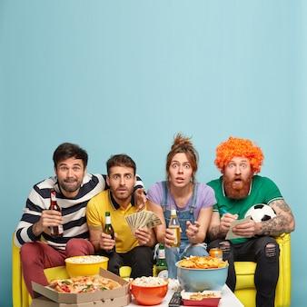 Impressionato quattro amici che trascorrono il tempo libero a casa, scioccati mentre guardano interessanti partite emozionanti, bevono birra fredda, fissano con gli occhi spalancati