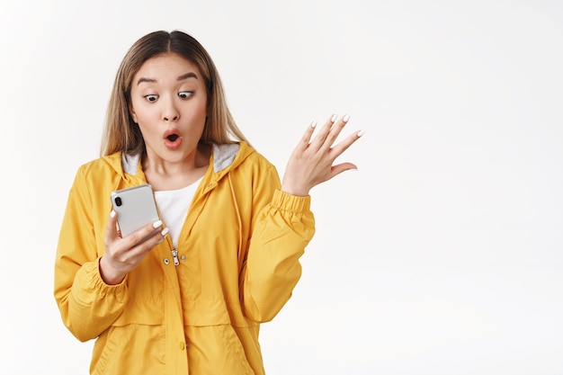 Impressed gasping ambushed shocked asian cute blond girl raising hand excited folding lips wow amazement emotions hold smartphone look phone screen astonished impressive article