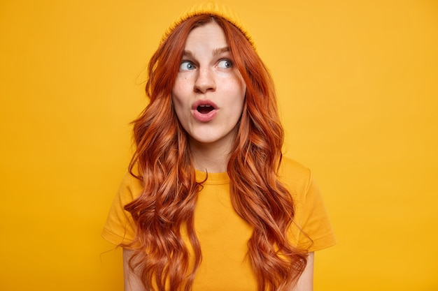 Impressed ginger girl keeps mouth opened from wonder notices something unbelievable focused away on unbelievable thing dressed in casual clothes