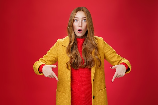感動した女の子は、カメラに向かって質問された驚きと興奮の飛び出る目から開いた口を見るものを信じることができません。人差し指で下を向いて質問し、赤い壁に驚いています。
