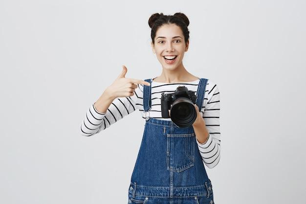カメラのディスプレイで指を指している印象的な女の子の写真家、素晴らしいショットを称賛、素晴らしいモデルの仕事
