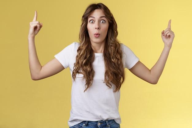 Впечатленная симпатичная девушка смотрит в камеру, поднимая указательные пальцы вверх