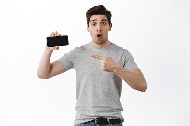 Impressed guy pointing at cool app, empty smartphone screen, showing moible phone display, standing against white wall