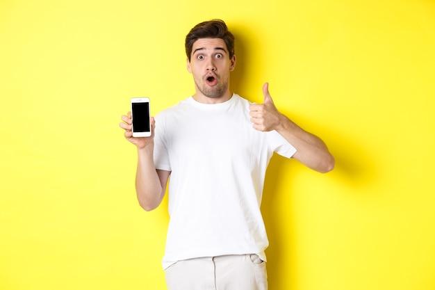 画面に素晴らしいスマートフォンアプリを表示し、親指を立てて、あえぎながら驚いて立っている感動した男
