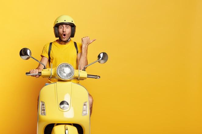 黄色いスクーターを運転するヘルメットを持つ感銘を受けた男