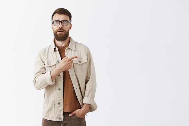 Impressed handsome bearded man in glasses posing against the white wall