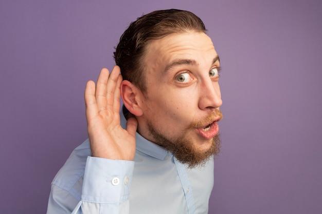 L'uomo biondo bello impressionato tiene la mano dietro l'orecchio sulla porpora