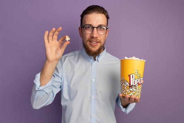광학 안경에 감동 된 잘 생긴 금발의 남자는 보라색 벽에 고립 된 팝콘 양동이를 보유