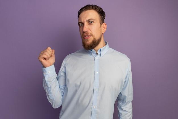 L'uomo biondo bello impressionato indica indietro isolato sulla parete viola