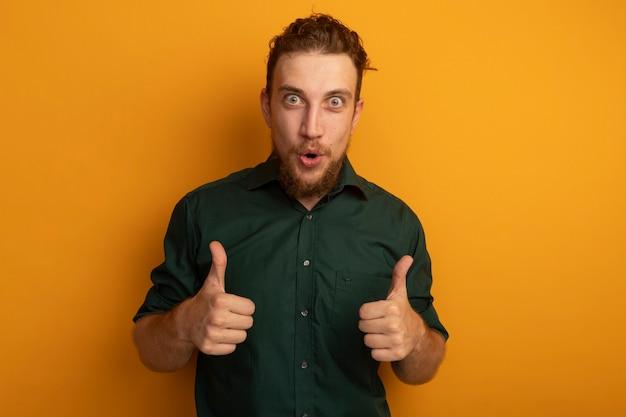 오렌지 벽에 고립 된 두 손의 감동 잘 생긴 금발 남자 엄지 손가락