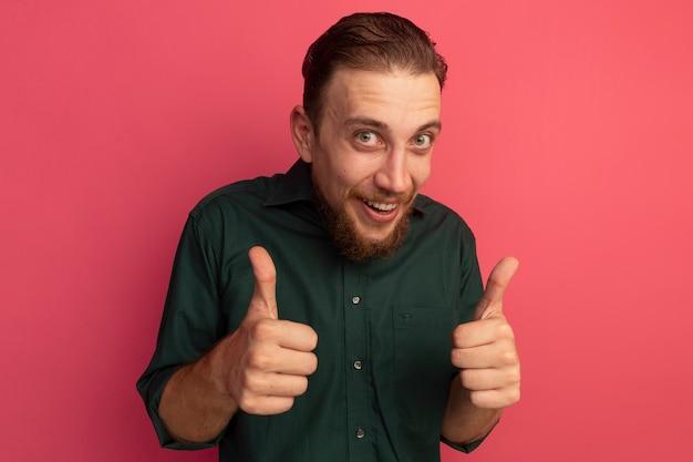 분홍색 벽에 고립 된 두 손의 감동 된 잘 생긴 금발의 남자 엄지 손가락