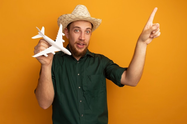 Impressed handsome blonde man with beach hat holds model plane and points up isolated on orange wall