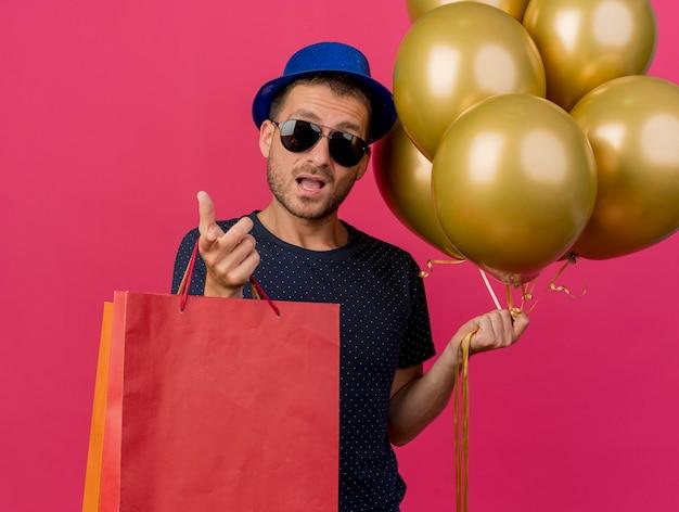 파란색 파티 모자를 쓰고 태양 안경에 감동 된 잘 생긴 백인 남자는 복사 공간이 분홍색 배경에 고립 된 카메라를 가리키는 헬륨 풍선과 종이 쇼핑백을 보유하고 있습니다.