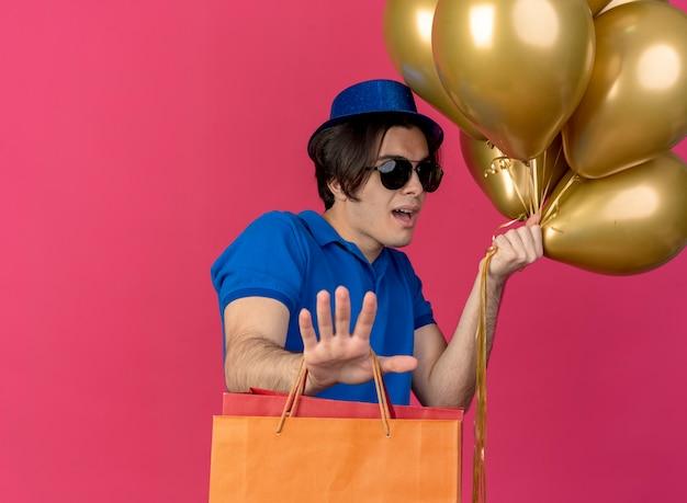 파란색 파티 모자를 쓰고 태양 안경에 감동 잘 생긴 백인 남자는 헬륨 풍선과 손을 뻗어 종이 쇼핑백을 보유하고 있습니다.