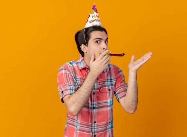 Impressionato bell'uomo caucasico che indossa un cappello da compleanno tenendo la mano aperta e soffiando il fischio di festa