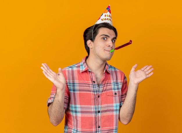 Impressionato bell'uomo caucasico che indossa un cappello di compleanno che tiene le mani aperte e soffia il fischio della festa party