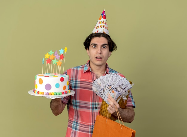 Impressed handsome caucasian man wearing birthday cap holds gift box paper shopping bag money and birthday cake