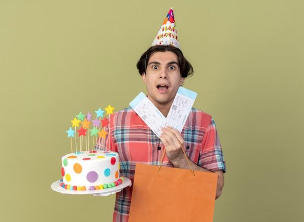 생일 모자를 쓰고 인상적인 잘 생긴 백인 남자가 종이 쇼핑백 항공권과 생일 케이크를 보유하고 있습니다.