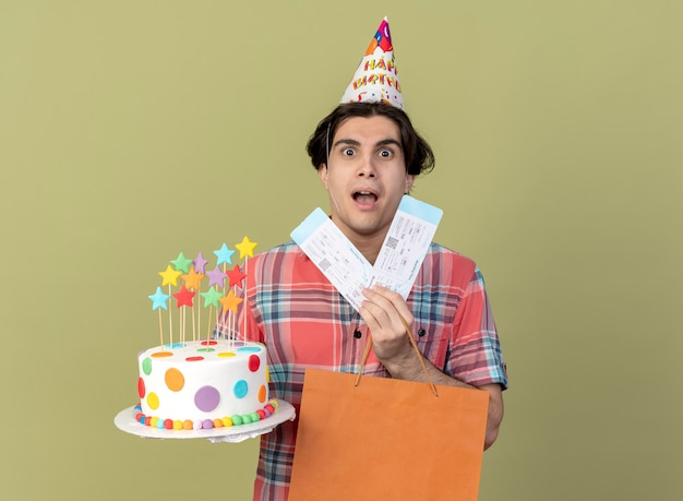 Impressed handsome caucasian man wearing birthday cap holds paper shopping bag air tickets and birthday cake