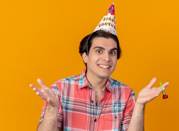 誕生日の帽子をかぶった印象的なハンサムな白人男性がパーティーの笛を吹く