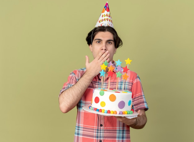 Impressed handsome caucasian man wearing birthday cap puts hand on mouth and holds birthday cake