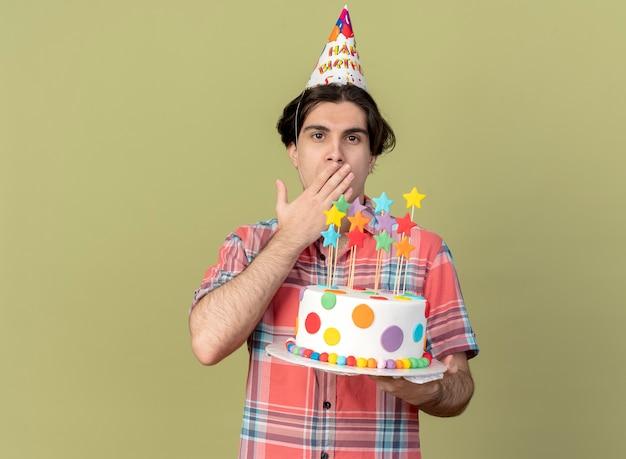 생일 모자를 쓰고 인상적인 잘 생긴 백인 남자가 입에 손을 넣고 생일 케이크를 들고 있습니다.