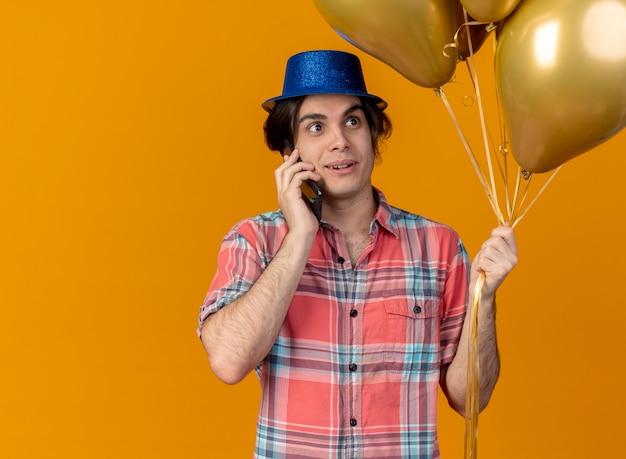 파란색 파티 모자를 쓰고 감동 잘 생긴 백인 남자가 전화로 이야기하는 헬륨 풍선을 보유하고 있습니다.