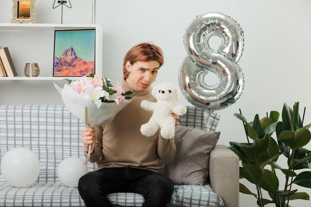 Un bel ragazzo impressionato durante la giornata delle donne felici che tiene in mano un bouquet con un orsacchiotto seduto sul divano in soggiorno