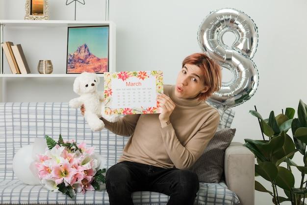 Un bel ragazzo impressionato durante la felice giornata delle donne che tiene in mano un orsacchiotto con il calendario seduto sul divano nel soggiorno