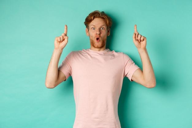 빨간 머리가 손가락을 가리키는 인상을 받은 잘생긴 남자, 민트 배경 위에 티셔츠를 입고 서 있는 프로모션 제안을 보여줍니다.