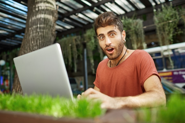 Impressed handsome guy working outdoors, freelancer with laptop sit in park and look wondered