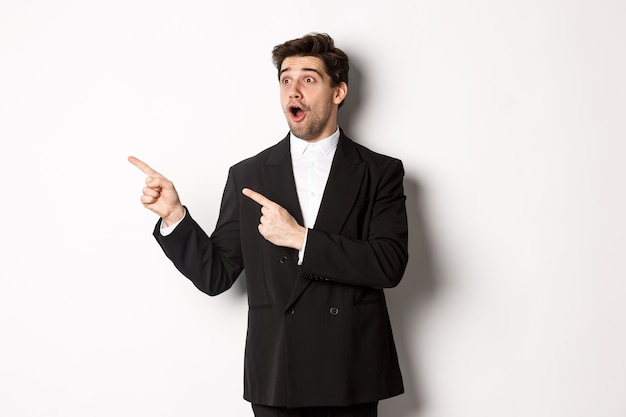 パーティースーツを着て、新年のプロモーションのオファーを見て、白い背景の上に立って、バナーに残された指を指して、印象的なハンサムな男