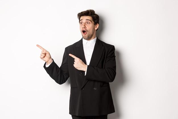 Impressionato bell'uomo in abito da festa, guardando l'offerta promozionale di capodanno e puntando il dito a sinistra sul banner, in piedi su sfondo bianco.