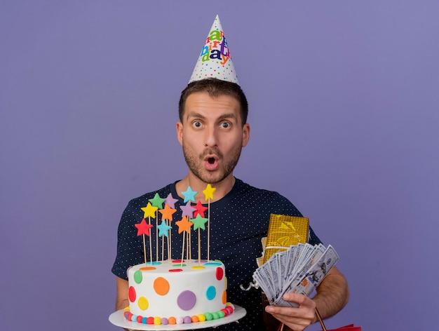 Impressionato bell'uomo che indossa il berretto di compleanno tiene il contenitore di regalo della torta di compleanno e soldi isolati sulla parete viola con lo spazio della copia