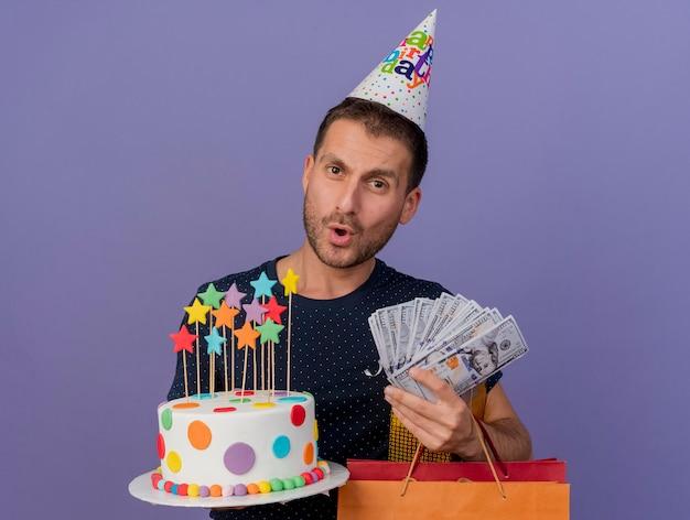 생일 모자를 쓰고 인상적인 잘 생긴 남자는 생일 케이크 종이 쇼핑백 선물 상자와 보라색 벽에 고립 된 돈을 보유하고 있습니다.