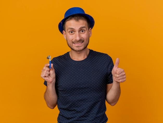 青いパーティーハットを身に着けている印象的なハンサムな男は親指を立てて、コピースペースでオレンジ色の壁に分離されたパーティーの笛を保持