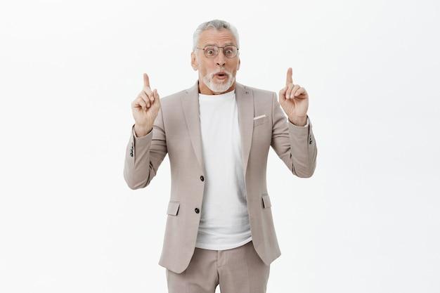 Впечатленный красивый старший мужчина в костюме, указывая пальцами вверх, изумлен